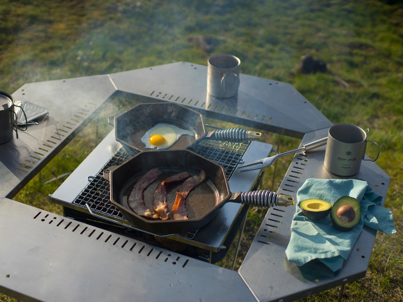 """8"""" and 10"""" cast iron skillet with bacon and eggs outdoors"""